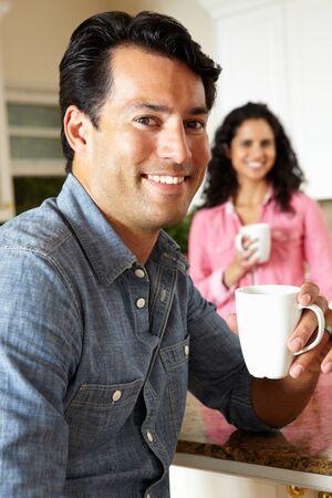 Hispanic couple relaxing in kitchen photo