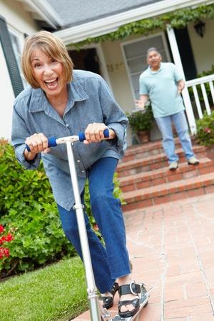 Senior Paar mit Kindern spielen die Roller Standard-Bild