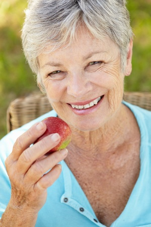 red haired woman: Senior woman eating apple
