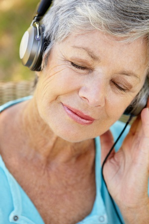 woman listening to music: Senior woman with headphone