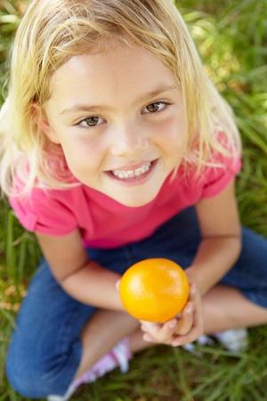 Portrait of happy girl with orange photo