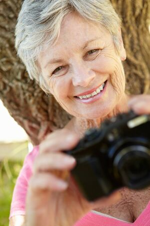 gray haired: Senior woman with camera