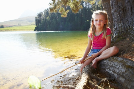 Happy girl fishing at lake photo