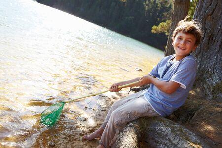 Happy boy fishing at lake Stock Photo - 11238996