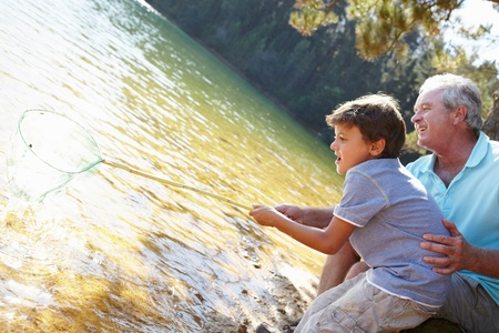 6 years: Man and boy fishing together Stock Photo
