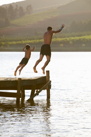 Young man with child jumping to water photo