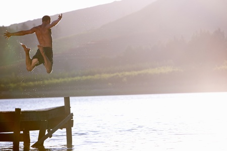 swimming costumes: Young man jumping into lake