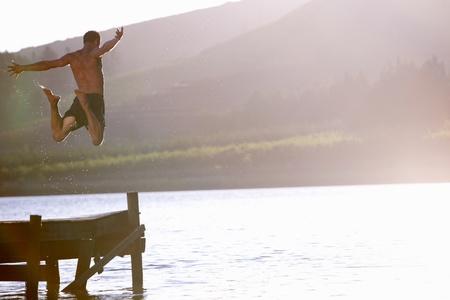 Young man jumping into lake Stock Photo - 11238200