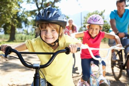 andando en bicicleta: Familia joven en bicicleta de paseo pa�s