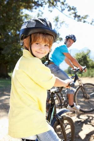 ni�os en bicicleta: Ni�o peque�o en paseo en bicicleta pa�s con pap�