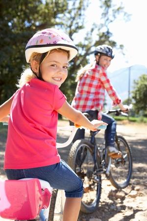ni�os en bicicleta: Ni�a en el pa�s de paseo en bicicleta con su mam�