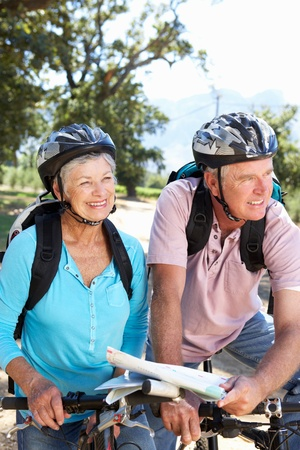Senior couple with map on country bike ride photo
