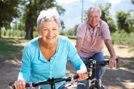 70s adult: Senior couple on country bike ride