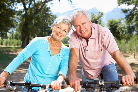 older women: Senior couple on country bike ride