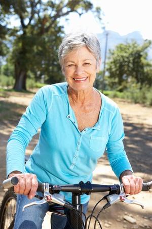 mujeres ancianas: Superior de la mujer en el paseo en bicicleta pa�s