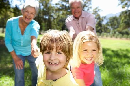 abuelos: Matrimonios de edad en el paseo por el campo con los nietos