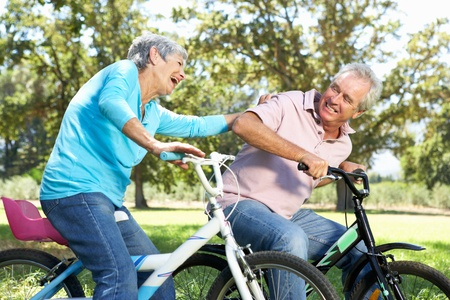 mature adult women: Senior couple playing on childrens bikes