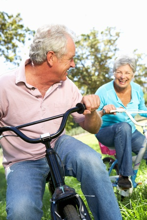 Senior couple playing on childrens bikes photo
