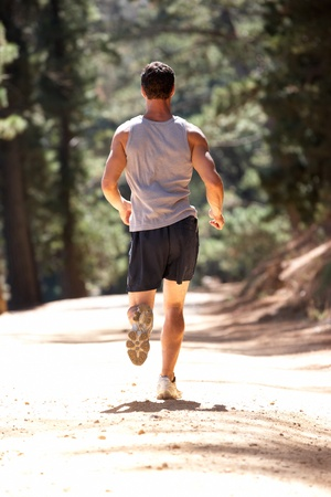 jogging track: Young man running along country lane Stock Photo