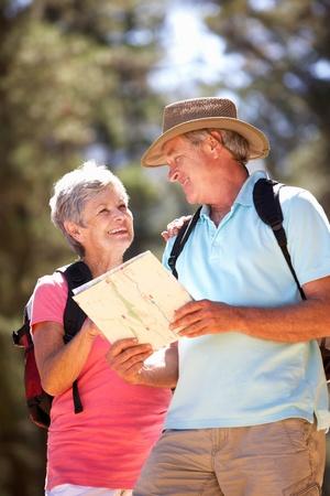 senioren wandelen: Senior paar het lezen van kaart op landelijke wandeling