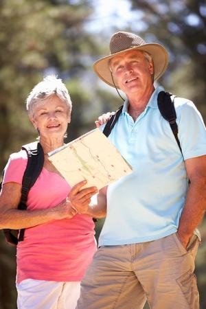 parejas caminando: Matrimonios de edad en la lectura de mapas paseo por el campo Foto de archivo