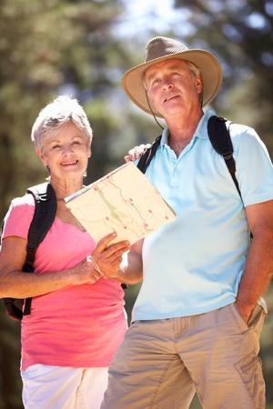 ramble: Senior couple reading map on country walk Stock Photo