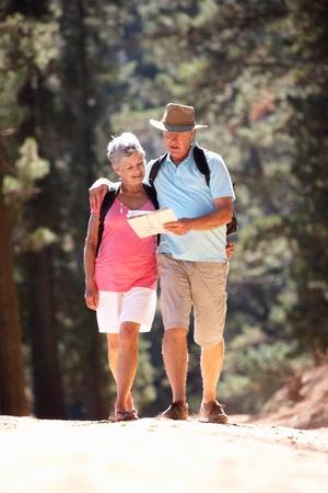 Senior couple reading map on country walk photo