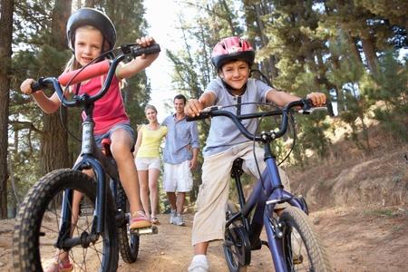 niños en bicicleta: Familia de paseo por el campo con las bicicletas