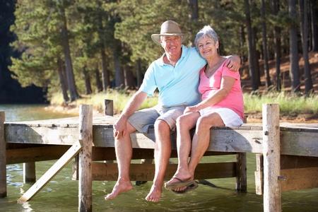 Senior couple sitting by lake photo