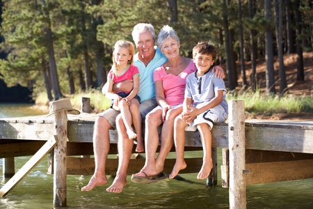a year older: Senior couple sitting by lake with grandchildren