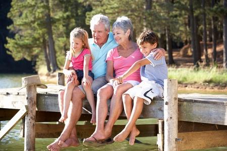 jubilados: Senior joven sentado al lado del lago con sus nietos Foto de archivo