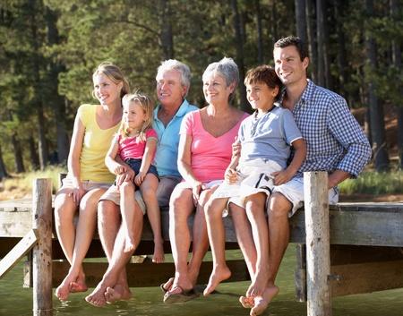 familia abrazo: 3 Generaci�n de la familia se sienta junto al lago