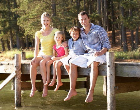 Young family sitting by lake photo
