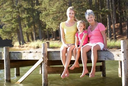 mother with daughter: Madre, hija y abuela sentada por el lago Foto de archivo