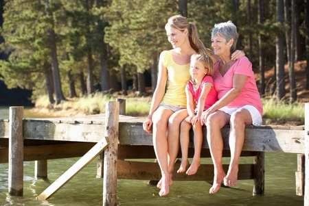 Mother,daughter and grandmother sitting by lake photo