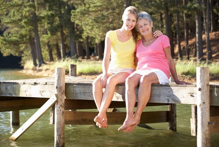 daughter mother: Mother and adult daughter sitting by lake