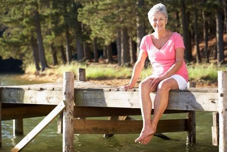 older women: Senior woman sitting by lake Stock Photo