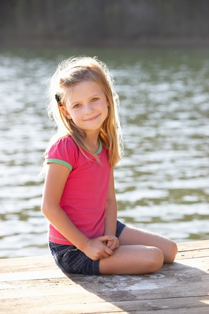 6 year old: Young girl sitting by lake Stock Photo