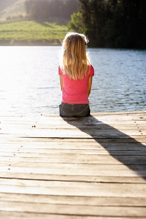 old pier: Young girl sitting by lake Stock Photo