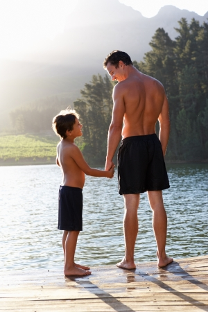 Father and son standing on jetty photo