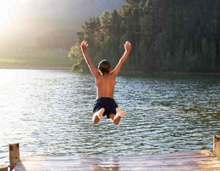 saltando: Muchacho joven que salta en el lago Foto de archivo