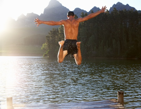 Young man jumping into lake photo