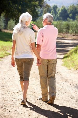 walk away: Senior couple on country walk Stock Photo