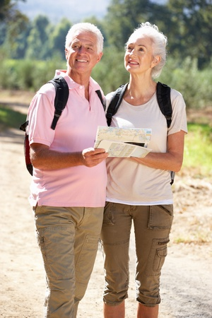 Senior couple reading map on country walk photo