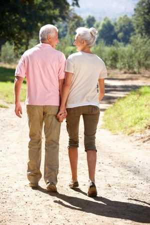parejas caminando: Senior pareja en el paseo por el campo