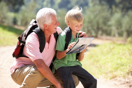Senior man reading map with grandson on country walk photo