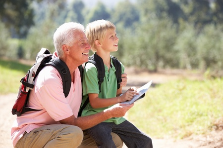 grandad: Senior man reading map with grandson on country walk