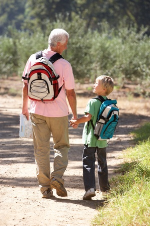 walk in: Senior man and grandson on country walk