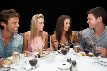 sharing food: Two young couples in restaurant