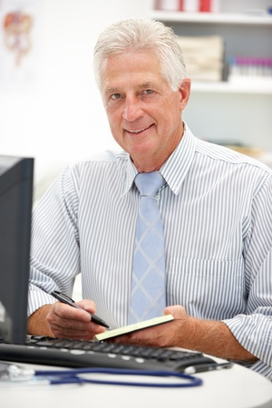 computerised: Senior doctor at desk Stock Photo